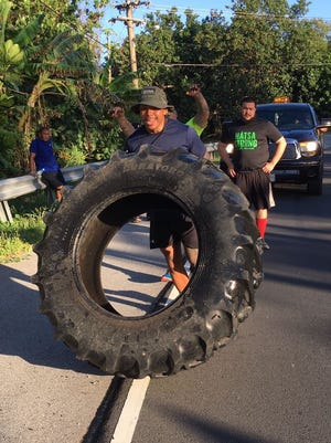 Fitness expert Ray Chargualaf flips a tire through Inalahan with the help of his team.