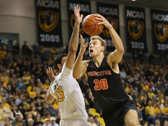 Nov 29, 2016; Richmond, VA, USA; Princeton Tigers forward Hans Brase (30) shoots the ball as Virginia Commonwealth Rams forward Ahmed Hamdy-Mohamed (23) defends in the first half at Stuart Siegel Center.