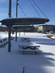 Picnic tables and benches at Mill Park sit outside Champlain Mills at the southeast edge of the Winooski Rotary on Tuesday. Critics of a proposed hotel project at an undeveloped site beyond the park say the park would be compromised. Photographed Feb. 14, 2017.