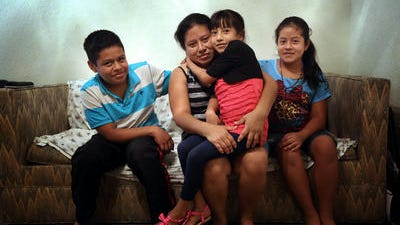 Modesta Escalante with her three children, Yeser, 14, from left, Yuri, 7, and Marialinda, 12, in their Hamilton apartment. The children and Modesta's niece recently made their way across the Mexican border into Arizona.