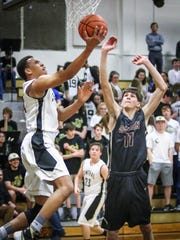 Central Magnet's Nick Hamlett goes for a layup while Cannon County's Trey Fann defends.