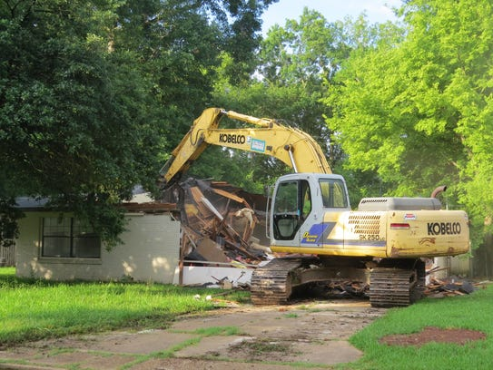 A track hoe demolishes a house in flood-prone Greenway