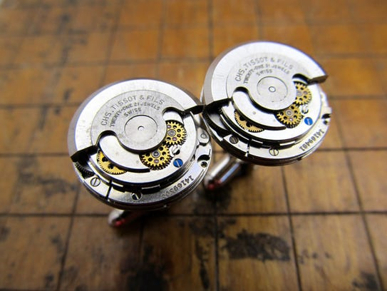 A pair of cufflinks made from vintage watch parts is