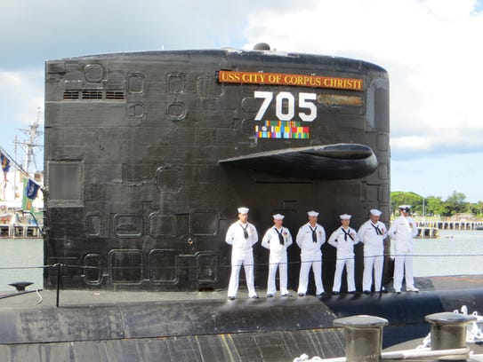 Sailors stand at rest aboard the USS City of Corpus