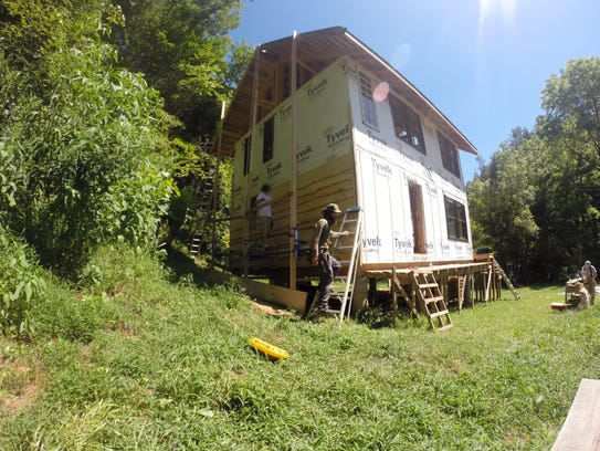 Crews put up white pine siding on a new home construction