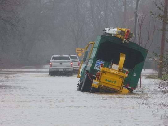 A tree-trimming truck sat stranded in flood water Tuesday