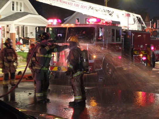 A firefighter gets hosed off after a fire in the 2600 block of South Chicago Avenue. One person was taken to the hospital with possible smoke inhalation.