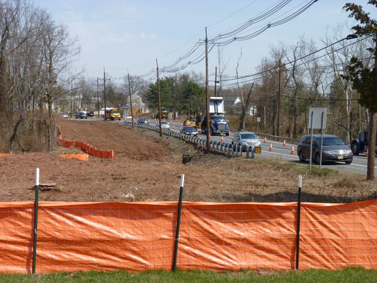 Traffic moves steadily as construction workers start