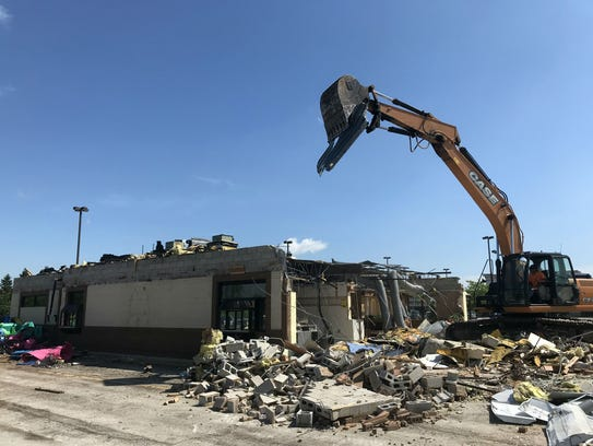 A demolition crew tears down the McDonald's at 9120