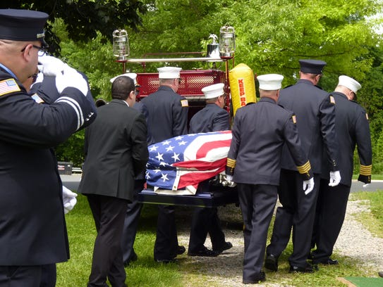 The casket of Gene De Cleene being carried to his burial
