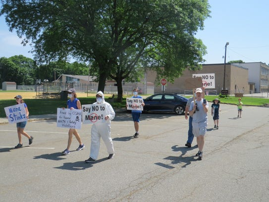 Protesters picket against a proposed fragrance factory