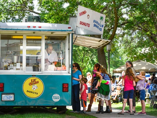 Shoppers stand in line for mini donuts during the Lemonade Art Fair Thursday, June 21, at St. Cloud State University.