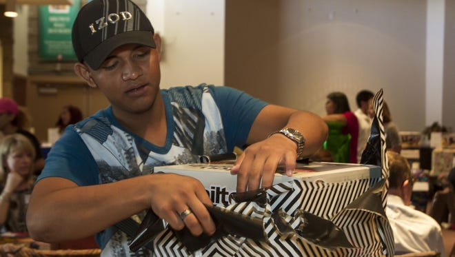 Ramon Alex Murillo opens his gift at the success shower hosted by the Arizona Friends of Foster Children Foundation at North Scottsdale United Methodist Church in Scottsdale. The foundation helps kids who age out of the foster care system.