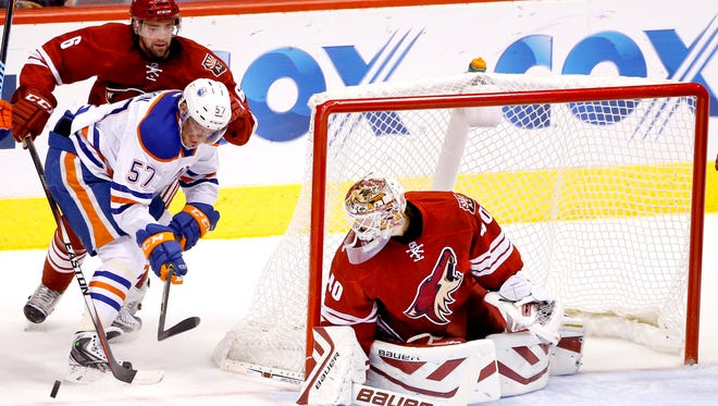 David Schlemko of the Coyotes (6) defends against David Perron (57) of Edmonton as he tries to settle the puck down in front of Coyotes goalie Devan Dubnyk during the first period of an NHL hockey game  on Tuesday, Dec. 16, 2014, at Gila River Arena in Glendale, Ariz.