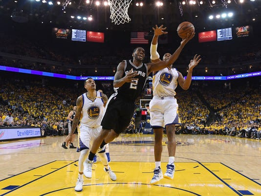 San Antonio Spurs forward Kawhi Leonard (2) shoots in front of Golden State Warriors forward Matt Barnes (22) and forward David West (3) during the first half of Game 1 of the NBA basketball Western Conference finals in Oakland, Calif., Sunday, May 14, 2017. The Warriors won 113-111. (Thearon W. Henderson/Getty Images via AP, Pool)