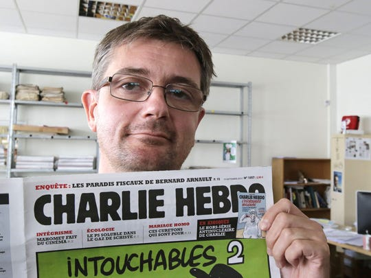 In this Sept.19, 2012 file photo, Stephane Charbonnier, also known as Charb, the publishing director of the satyric weekly Charlie Hebdo, displays the front page of the newspaper as he poses for photographers in Paris.