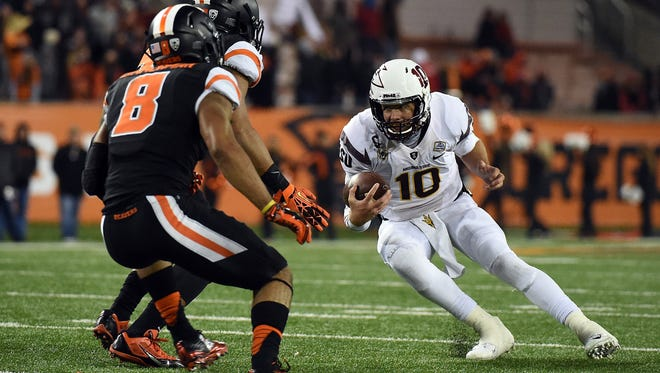 Defensive end Jaswha James and safety Tyrequek Zimmerman of Oregon State close in on ASU quarterback Taylor Kelly on Nov. 15, 2014 in Corvallis.