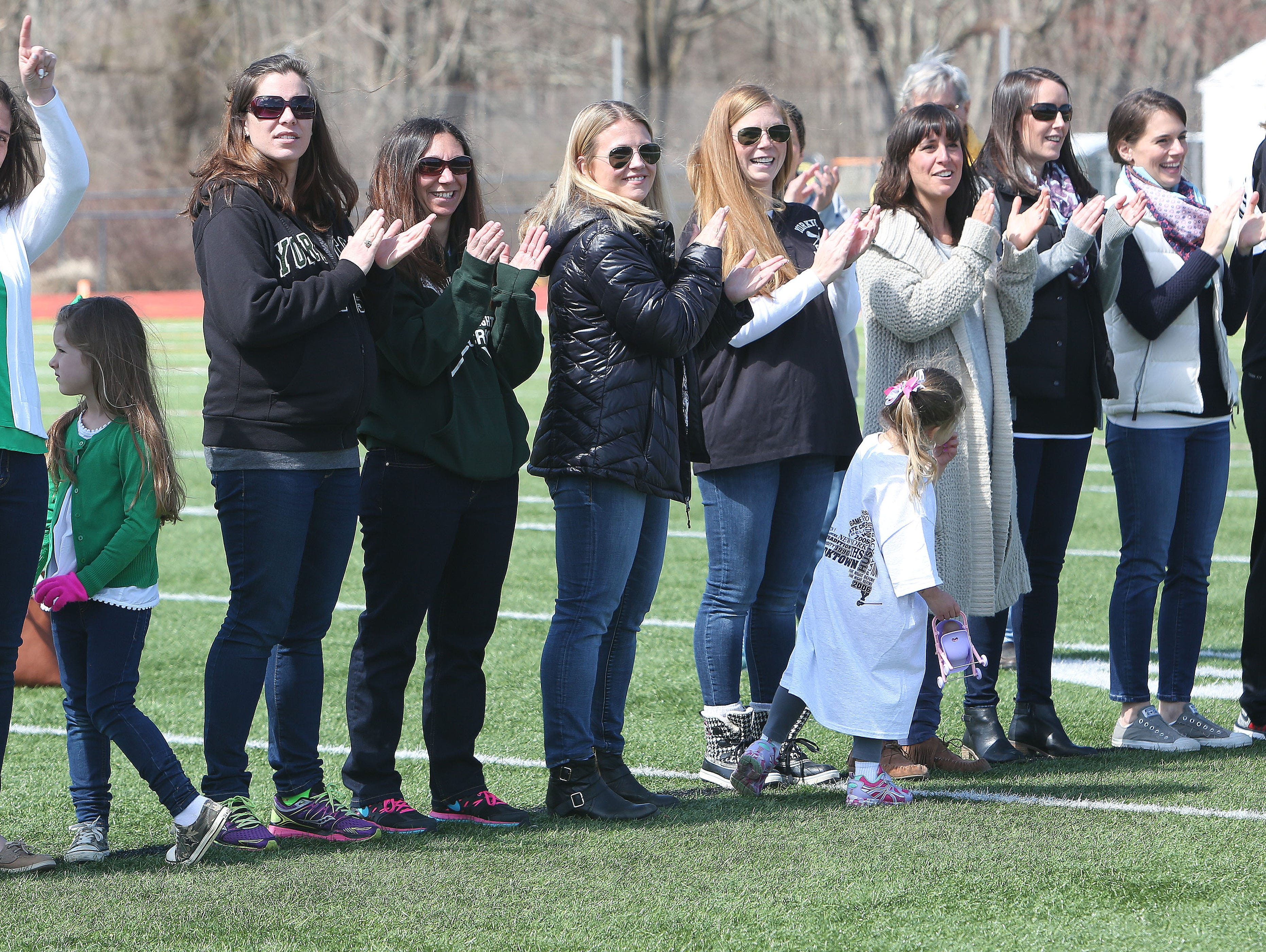 Former Yorktown girls lacrosse players wave to the crowd as they are introduced during a halftime ceremony honoring the 1996 and 2006 state championship teams at Yorktown High School during Saturday's game against Arlington.