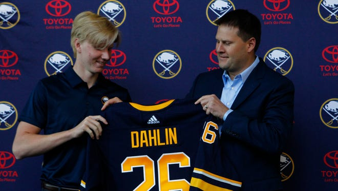 No. 1 draft pick Rasmus Dahlin, left, receives his Sabres jersey from general manager Jason Botterill.