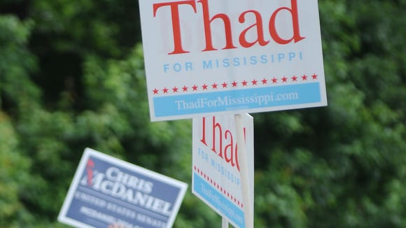 Supporters of U.S. Sen. Thad Cochran and challenger, state Sen. Chris McDaniel, campaign along Spillway Road near the voting precinct located at the Rankin County Community Center on Tuesday.