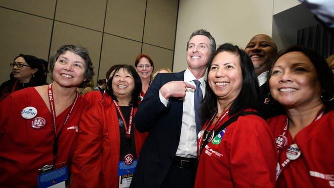 Democratic gubernatorial candidate Gavin Newsom, center, poses with supporters after a town hall meeting at the 2018 California Democrats State Convention Saturday, Feb. 24, 2018, in San Diego. California and America should look to a third party to solve problems rather than expecting relief from the established, mainline ones that have shown they can't get the job done.