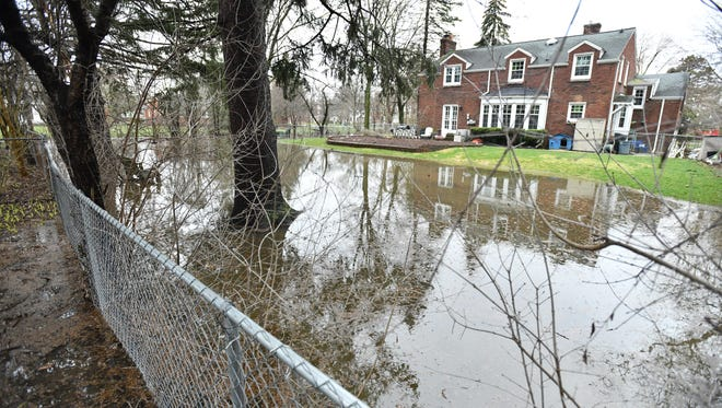 Water floods a backyard near Bloomfield Drive and San Quentin Drive in Lathrup Village Monday morning.