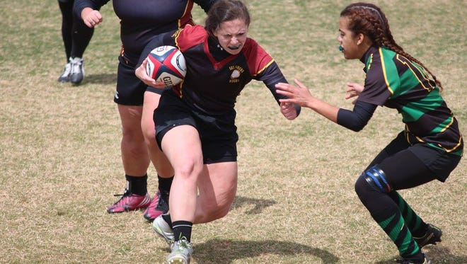 Gabby Hiken, a senior for Salisbury's rugby team, fights off a tackler.