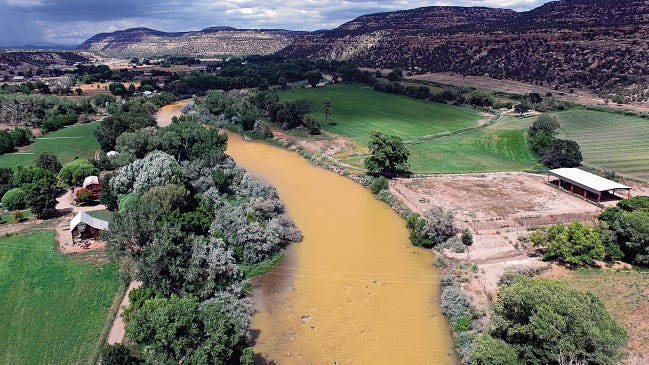 The Animas River flows on Aug. 7 near the Colorado-New Mexico line after the Gold King Mine spill released more than 3 million gallons of toxic wastewater into the river.
