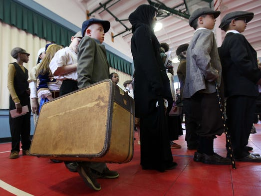 Ten-year-old Ricky Lloyd holds onto a large suitcase while pretending to emigrate from Sisley during a simulation of Ellis Island for a fourth-grade history class project at the Odyssey Charter School, Wednesday, April 16, 2014.