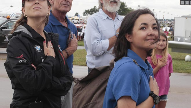 Suzanne Herrick, aerobatic pilot Sean D. Tucker, Harrison Ford and Jodie Gawthrop stand with their hands over their hearts as the national anthem is played at EAA AirVenture Thursday, July 28, 2016 in Oshkosh, Wis. Ford took Gawthrop, 16, of West Chester Ill. on the two millionth flight of the Young Eagles program.