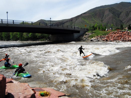 "A stand-up paddleboarder surfs the ""G-Wave"" at Glenwood"