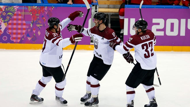 Latvia forward Lauris Darzins (10) celebrates with teammates after scoring an empty net goal against Switzerland in a qualification game at the Sochi Olympics.