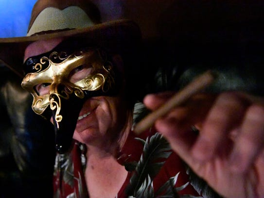 Gary Pierce's ornate mask didn't seem to affect his cigar Saturday during the Dolls Ball: Unmasking Domestic Violence at the Zone Bar & Grill.