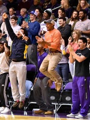 Furman football players cheer during the basketball