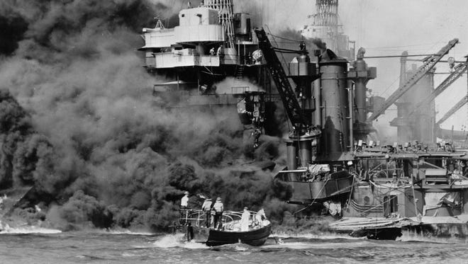A small boat rescues a seaman from the USS West Virginia as it burns at Pearl Harbor on Dec. 7, 1941.