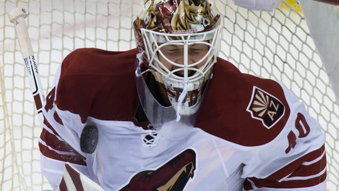 Arizona Coyotes goalie Devan Dubnyk stops a shot by Vancouver Canucks' Chris Higgins during the second period of an NHL hockey game in Vancouver,British Columbia, on Friday, Nov. 14, 2014.