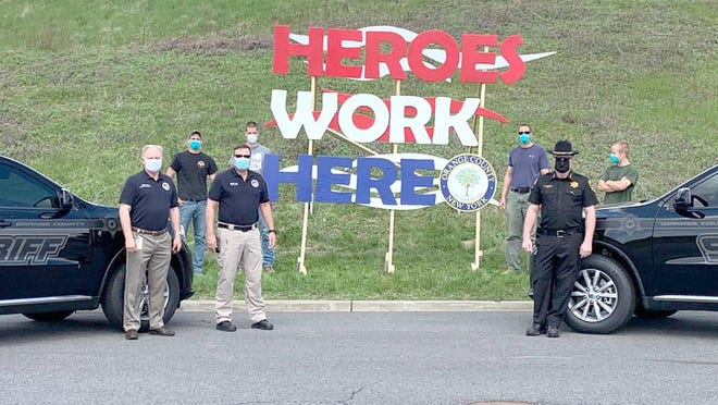 """Members of the Bruderhof Community, led by Ben Barth, unveiled a giant """"heroes work here"""" sign at the crossroads of the Orange County Sheriff's Office and the Emergency Services Center. From left, Sgt. Andrew Frank, Sgt. Justin Butterfield, Deputy Commissioner Craig Cherry, Commissioner Brendan Casey, Sheriff Carl E. DuBois and Captain Paul Arteta. Back row: Royce Durgin, Logan Barth, Ben Barth and Joel Marchant."""