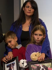 Ashton Collins (left, 7) holds a photo of Carson, and his sister Alexis Collins (9) holds a photo of Daisy, while they attend a press conference with their mom, Valerie Collins, December 23, 2014, at the Schill Law Group office, 8700 E. Via de Ventura, Scottsdale.  Both of the Collins' dogs died in June at the Green Acre Dog Boarding kennel.