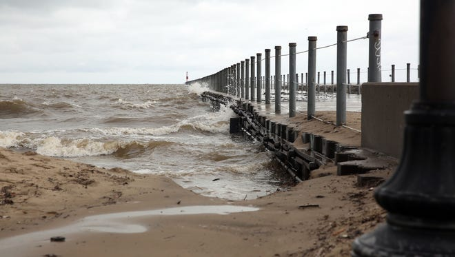 High waves from Lake Ontario are washing up over the pier at Ontario Beach Park.