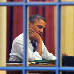 President Obama works at his desk in the Oval Office last year.