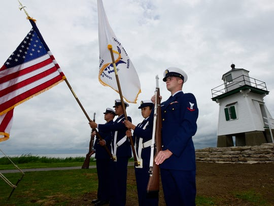 Fireman Zachary Walsh, from left, BM3 Isaac Padilla, SN Angelique Castro and BM3 Tyler Fields from the U.S. Coast Guard's Marblehead station during the dedication and lighting ceremony for the Port Clinton Lighthouse. In use from 1896-1952 then decommissioned, the lighthouse has been restored and outfitted with a Fresnel lens.