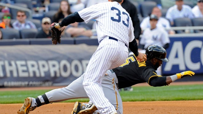 Yankees first baseman Kelly Johnson (33) tags out the Pirates' Josh Harrison after a rundown in the fifth inning during the second game of Sunday's doubleheader.