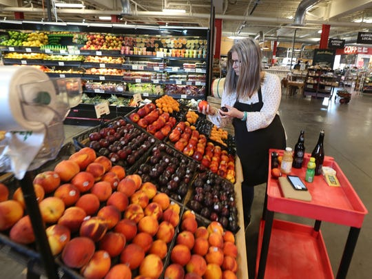 Amy Jerman picks out fruits ordered as she fills an online delivery order.