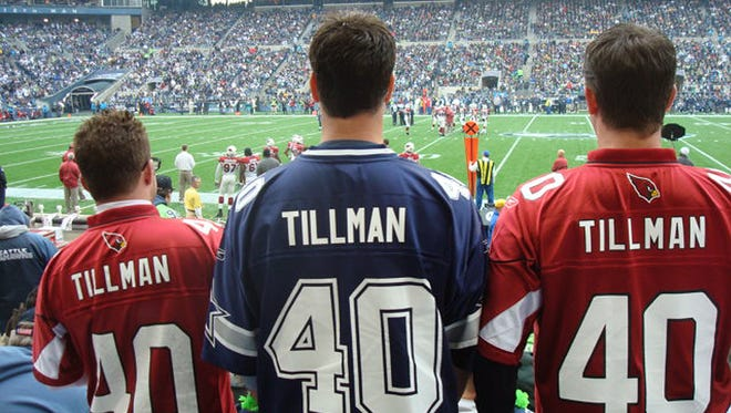 Three veterans, wearing football jerseys with Pat Tillman's name and number, enjoy a Cardinals football game in Seattle.  Credit: Veteran Tickets Foundation.