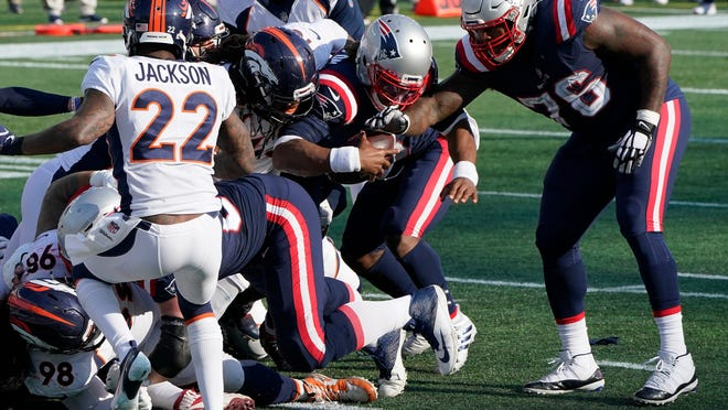 New England Patriots quarterback Cam Newton, center, bulls his way to the goal line and a touchdown in the second half of an NFL football game against the Denver Broncos, Sunday, Oct. 18, 2020, in Foxborough, Mass.