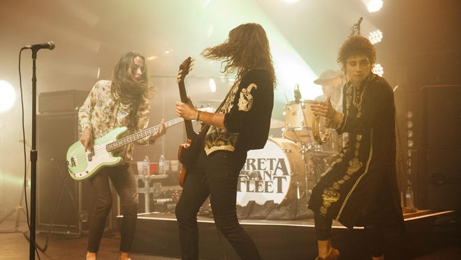 Greta Van Fleet, from left, brothers Sam, Jake and Josh Kiszka and drummer Danny Wagner, background, rock out at the Fillmore Detroit in May.