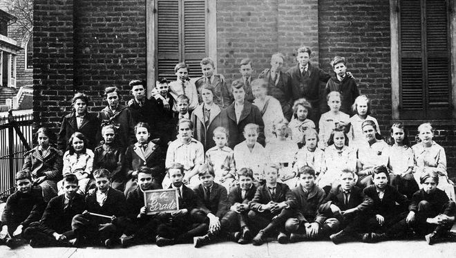 "Two of the students in this circa 1913 photo are holding a chalkboard that reads ""6-A Grade."" They are posing outside a small brick structure at the west end of the Stonewall Jackson Grammar School on West Beverley St., across from Trinity Church. It is possible that some of these students participated in the Civic Club essay contest, ""How to Make and Keep a Clean City."""