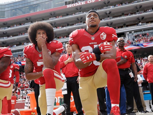 FILE - In this Oct. 2, 2016 file photo, San Francisco quarterback Colin Kaepernick, left, and safety Eric Reid kneel during the national anthem before an NFL football game against the Dallas Cowboys in Santa Clara, Calif. Reid says his Christian faith is the reason why he joined former teammate Colin Kaepernick in kneeling for the anthem. (AP Photo/Marcio Jose Sanchez, File)