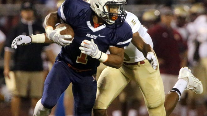 Blackman's Amauri Burks runs the ball as he is tackled by Riverdale's Jarek Campbell on Friday.