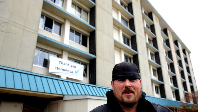 "Mike Karl stands outside the Magnuson Hotel last fall in Lansing. The hotel, known to many as Lansing's ""homeless hotel,"" closed on Friday. Karl announced Tuesday that his organization has partnered with a Williamston group, Harvest House Ministries, to buy a 52-room motel in Lansing Township."